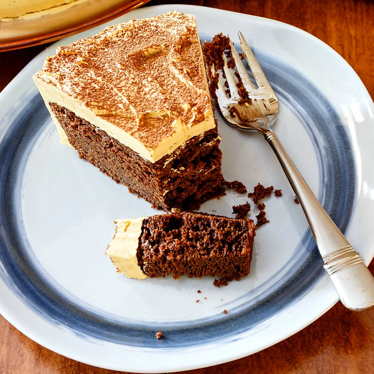 A slice of chocolate cake with cocoa powder-dusted caramel buttercream on a blue plate with a fork.