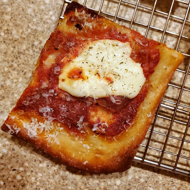 A close up shot of one rectangular corner piece of grandma pizza topped with ricotta cheese and tomato sauce.