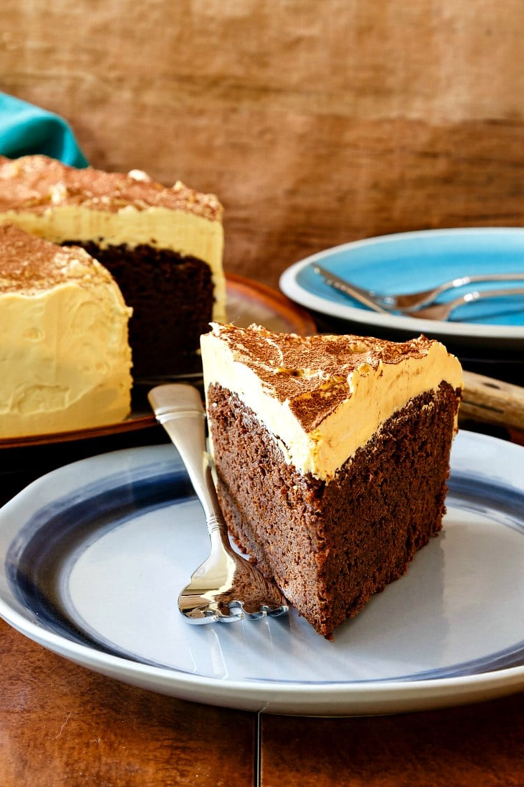 A slice of chocolate stout cake with a thick layer of caramel frosting on a blue plate.