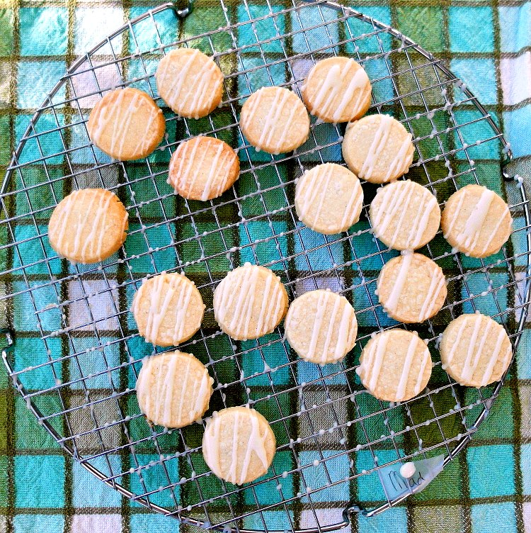 overhead shot of 18 round shortbread cookies with white icing drizzled on them on a cooling rack
