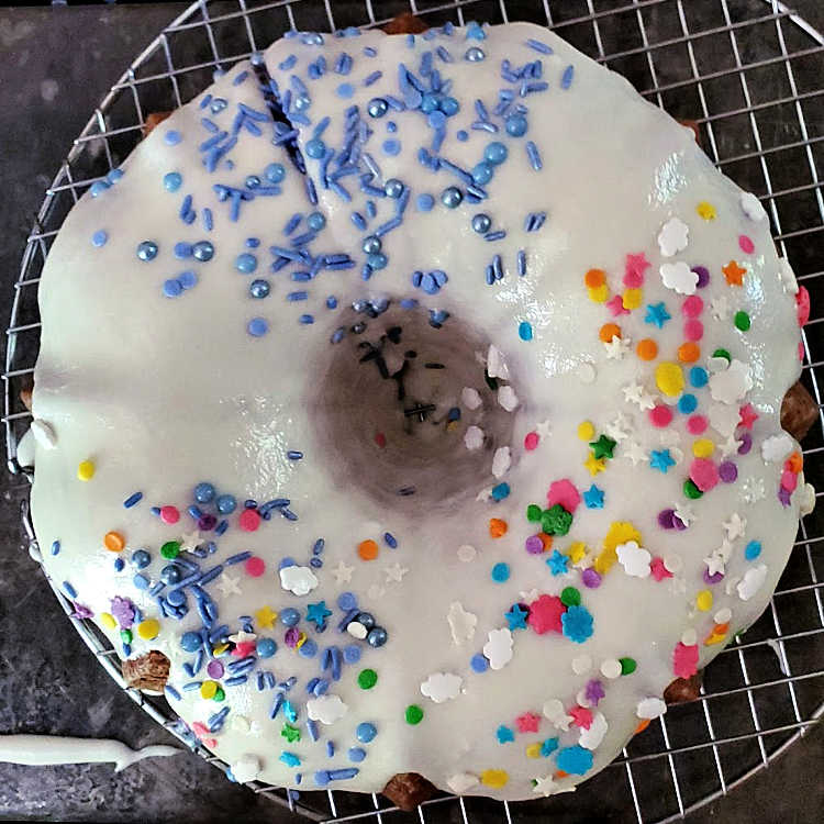 An overhead shot of glazed cake on a cooling rack with different sprinkles on it.
