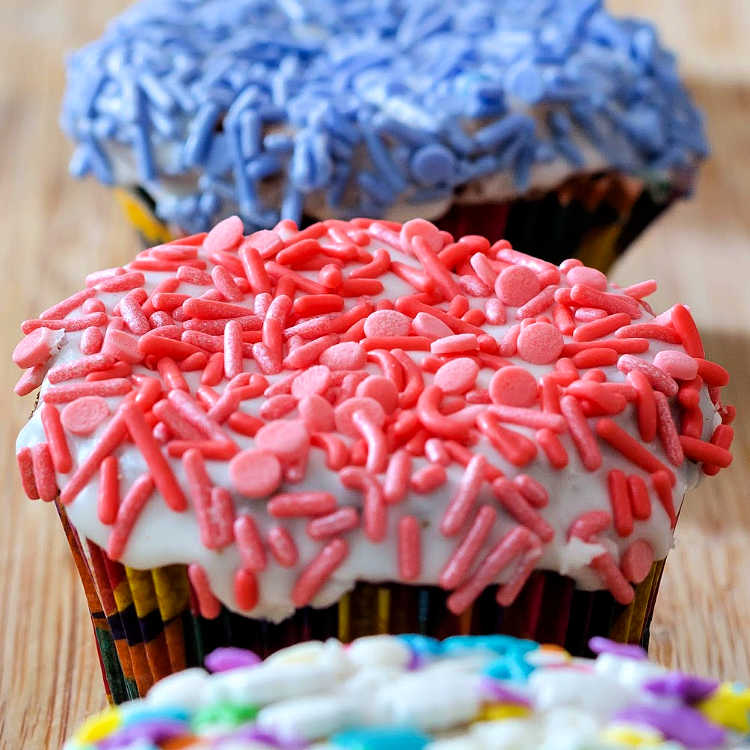 Close up shot of brown sugar cinnamon pound cake baked as cupcakes with a glazed top and covered in pink sprinkles, blue sprinkles on cup cake in the background.