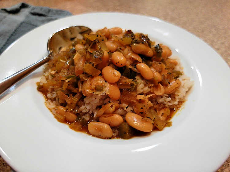a dish of vegan great northern beans over rice with a spoon in it