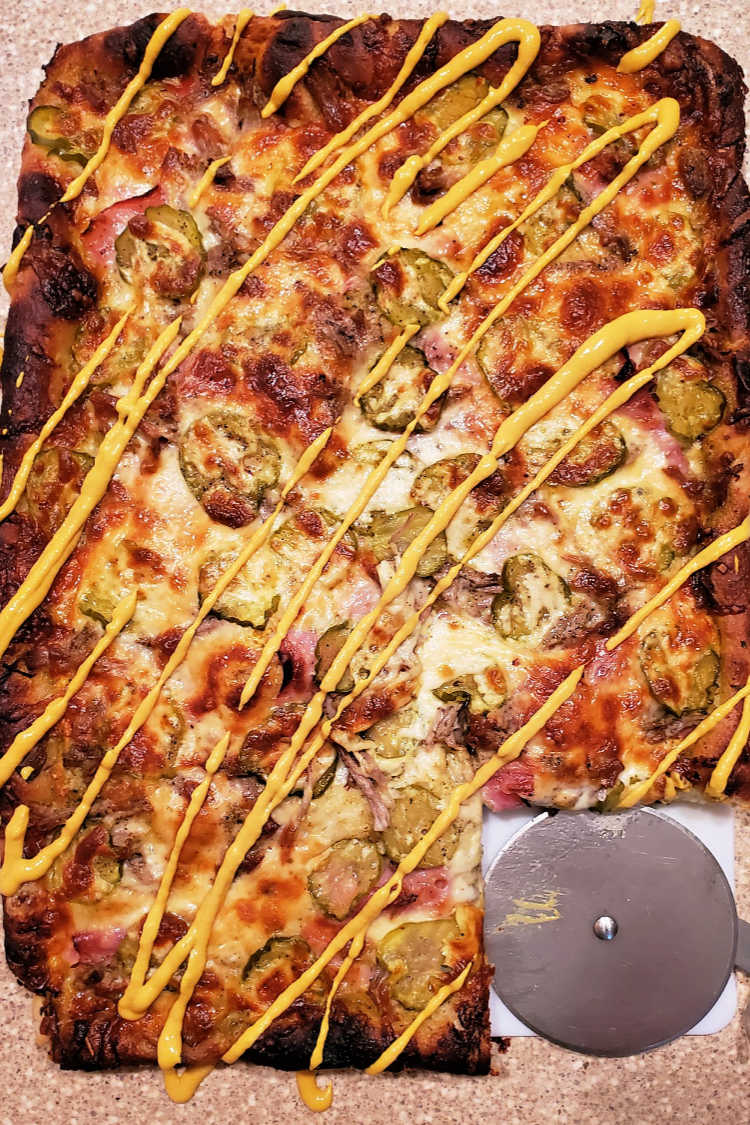 A whole cubano pizza with zigzags of yellow mustard on it and one slice cut out.