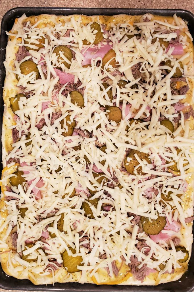 Overhead shot of a fully loaded cubano pizza before baking.