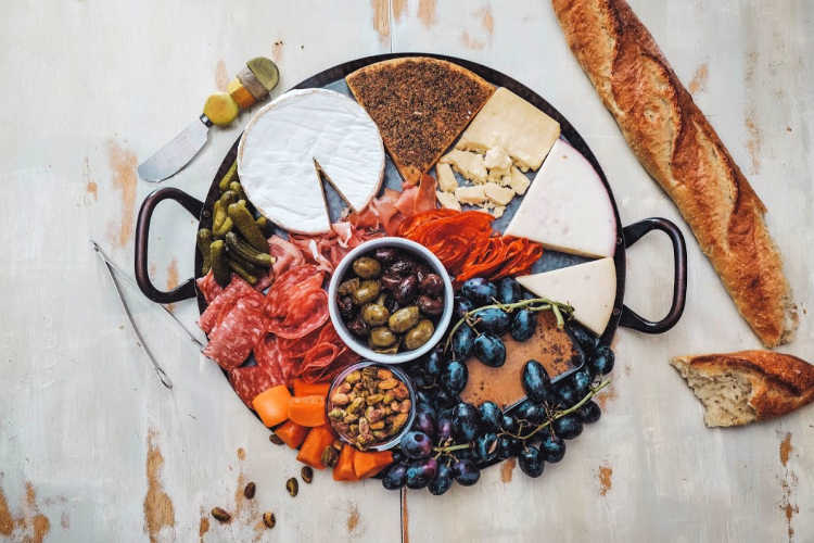 Overhead shot of round tray with cheese, pickles, olives, fruit, cured meat, and a torn baguette.