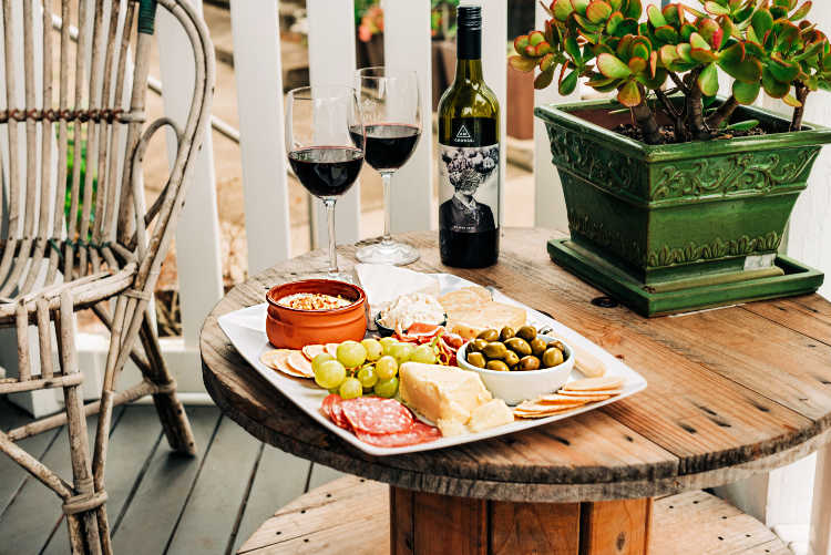 A cheese board with 2 glasses of wine, ready for serving on a porch.