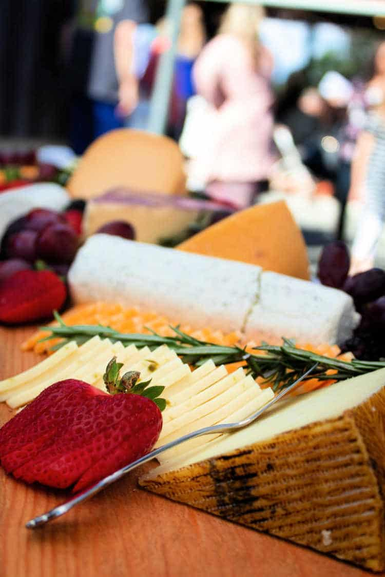 A log of goat cheese, a wedge of hard cheese and slices of cheese with a sliced strawberry and herbs on a board.