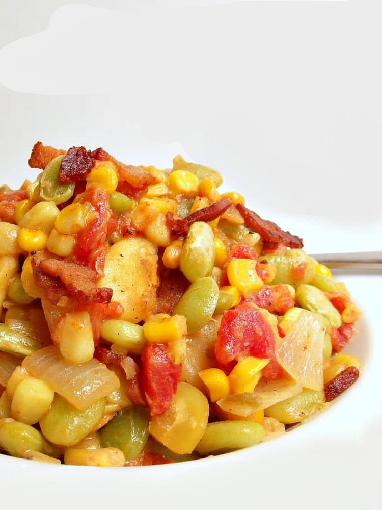 A mound of spicy succotash with corn, lima beans, fava beans and bacon on a white plate.