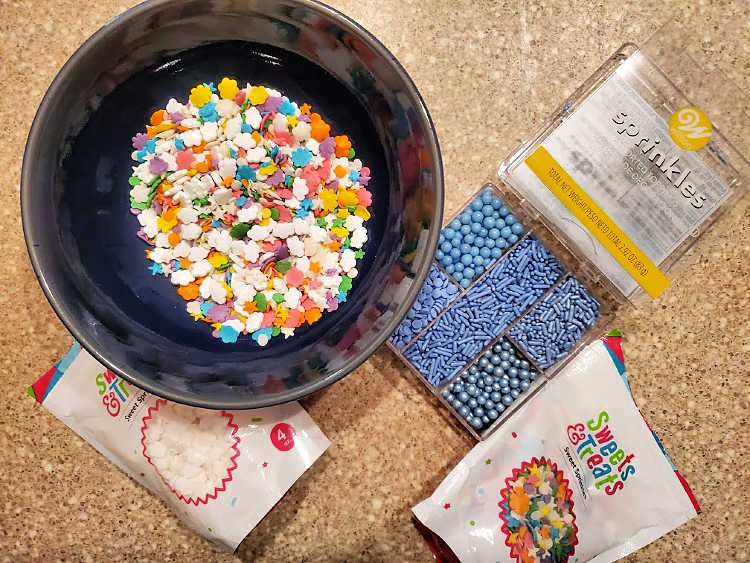 A bowl of multi colored sprinkles and bags of miscellaneous sprinkles.