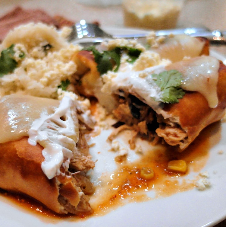 A chicken chimichanga with melted cheese and sour cream cut open so you can see the filling.