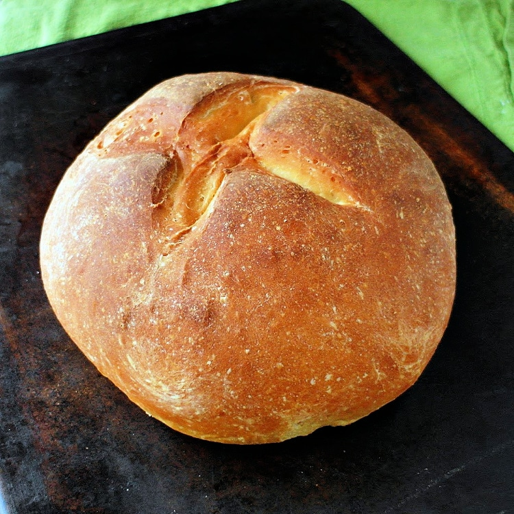 a round loaf of communion bread on a dark brown baking stone