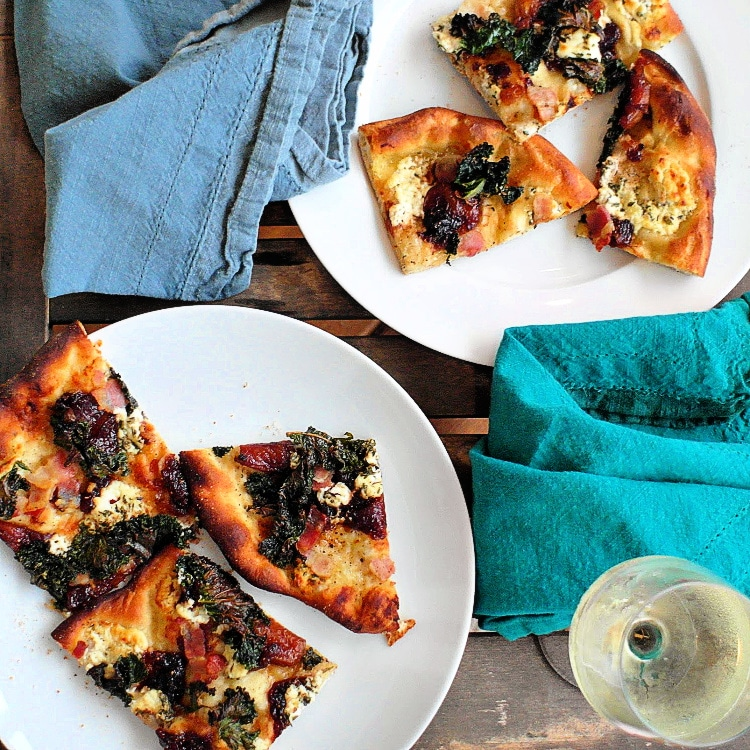 Cooked pizza with savory fig jam, kale, goat cheese, and bacon, cut up on white plates.