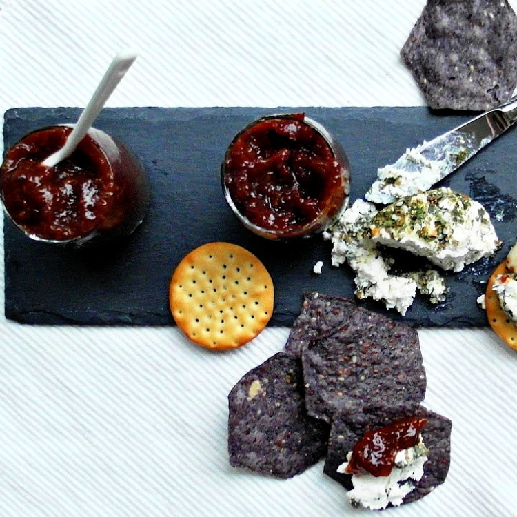 Overhead shot of blue tortilla chips, herbed goat cheese, crackers, and savory fig jam.