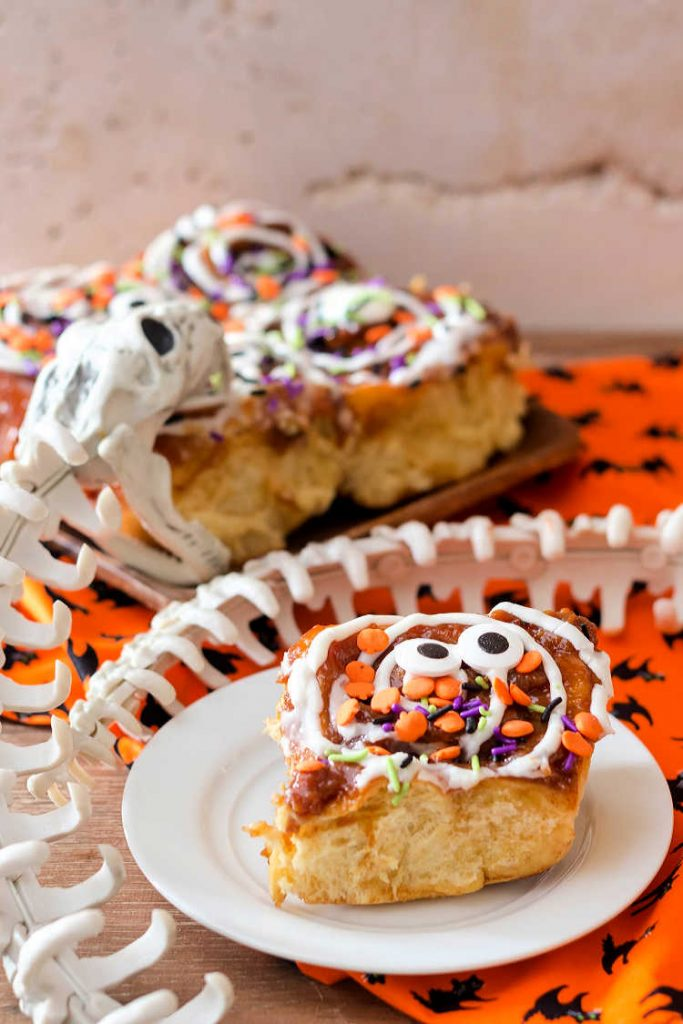 A cinnamon roll decorated for Halloween on a plate with a plastic snake skeleton.