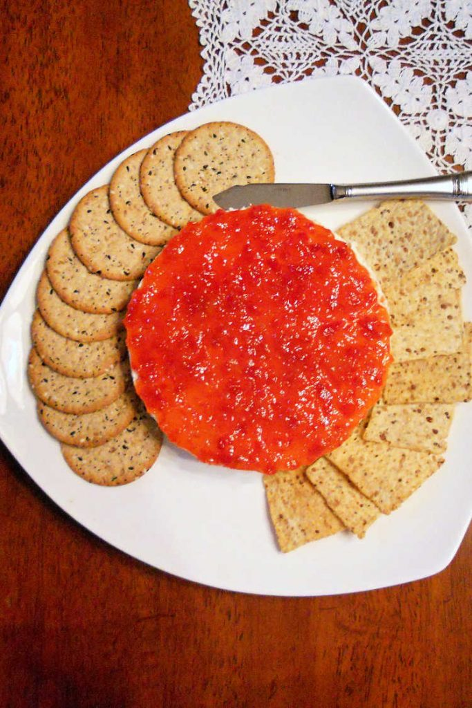 Overhead shot of savory cheesecake topped with pepper jelly with crackers on a white plate.