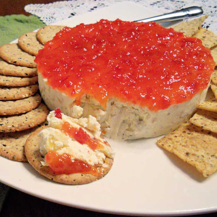 A savory cheesecake topped with pepper jelly spread over the top. A scoop has been taken out and smeared on a cracker. The cheesecake is surrounded with crackers on a white plate.
