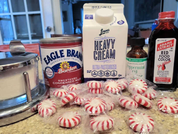Ingredients for homemade peppermint ice creams: salt, sweetened condensed milk, heavy cream, peppermint oil, red food coloring, and crushed mints.