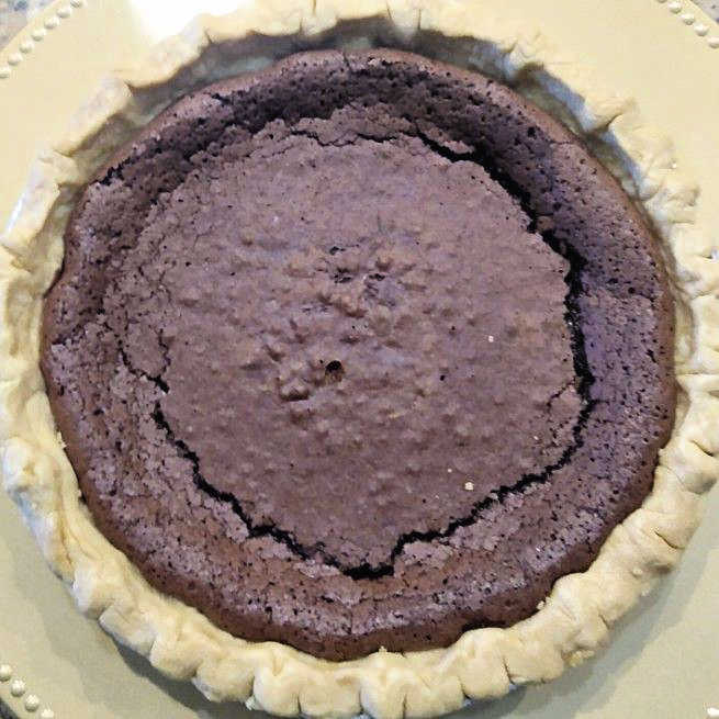 Overhead photo of whole chocolate chess pie on a platter.