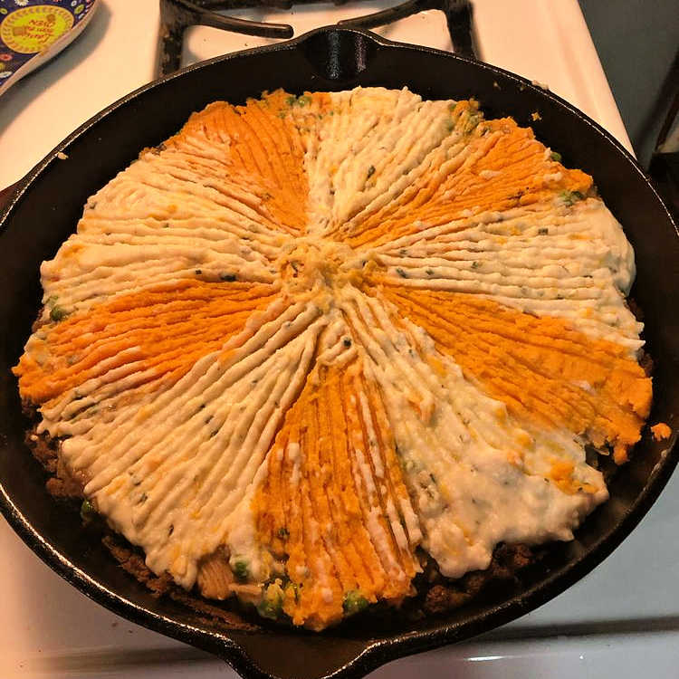 A shepherd's pie in a skillet topped with a mixture of mashed potatoes and mashed sweet potatoes.