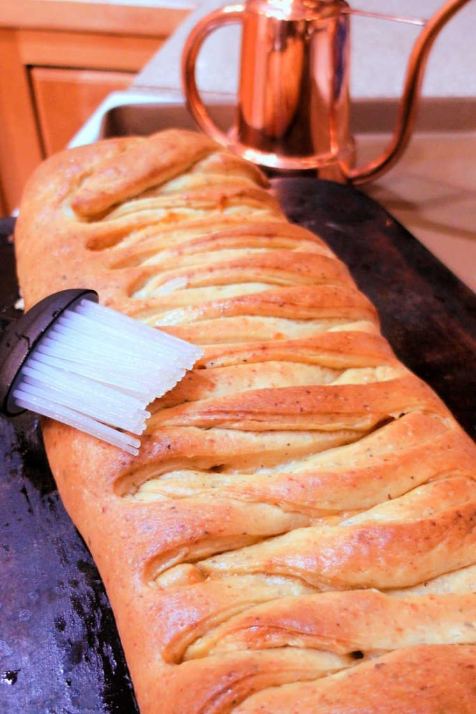 A whole baked braided pepperoni bread loaf.