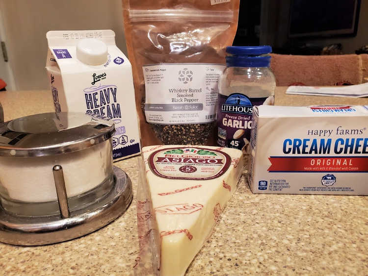 Kosher salt, heavy cream, smoked black pepper, freeze dried garlic, cream cheese, and Asiago cheese on a counter.