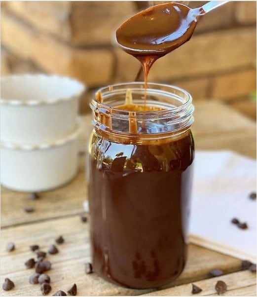 A jar of hot fudge sauce with a spoon in it.