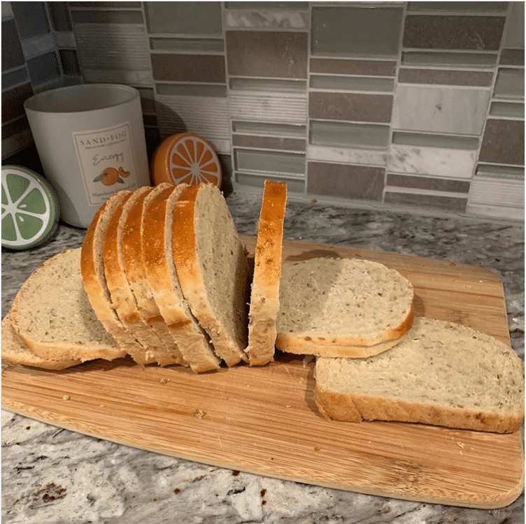 A wooden cutting board with a sliced loaf of bread on it. Some of the slices are lying down and others are still upright on the board.