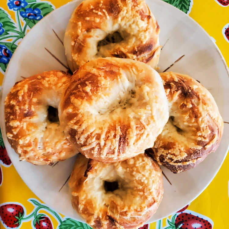 Overhead shot of  a pile of asiago bagels on a plate.