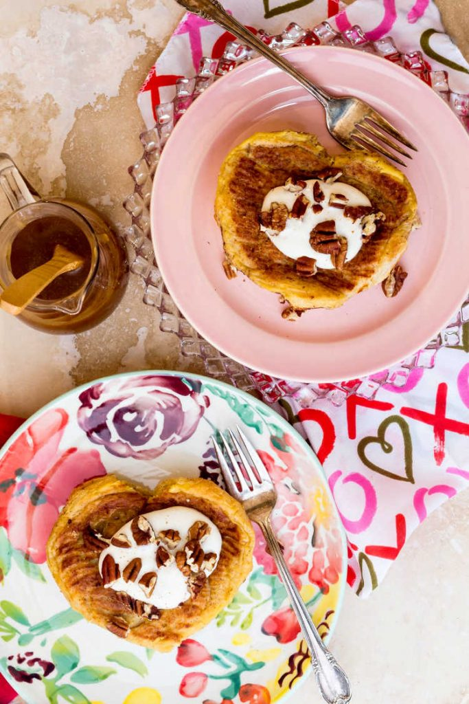 Overhead shot of 2 stuffed French toasts in the shape of hearts with cream and chopped pecans, one a floral plate and one on a pink plate.