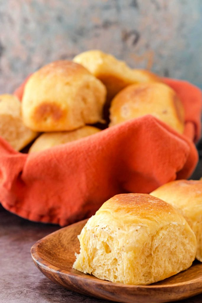Basket of rolls with an orange napkin and a cheese roll on a wooden plate.