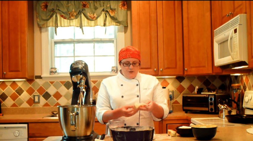 pastry chef in a kitchen with a mixer showing people how to do the creaming method