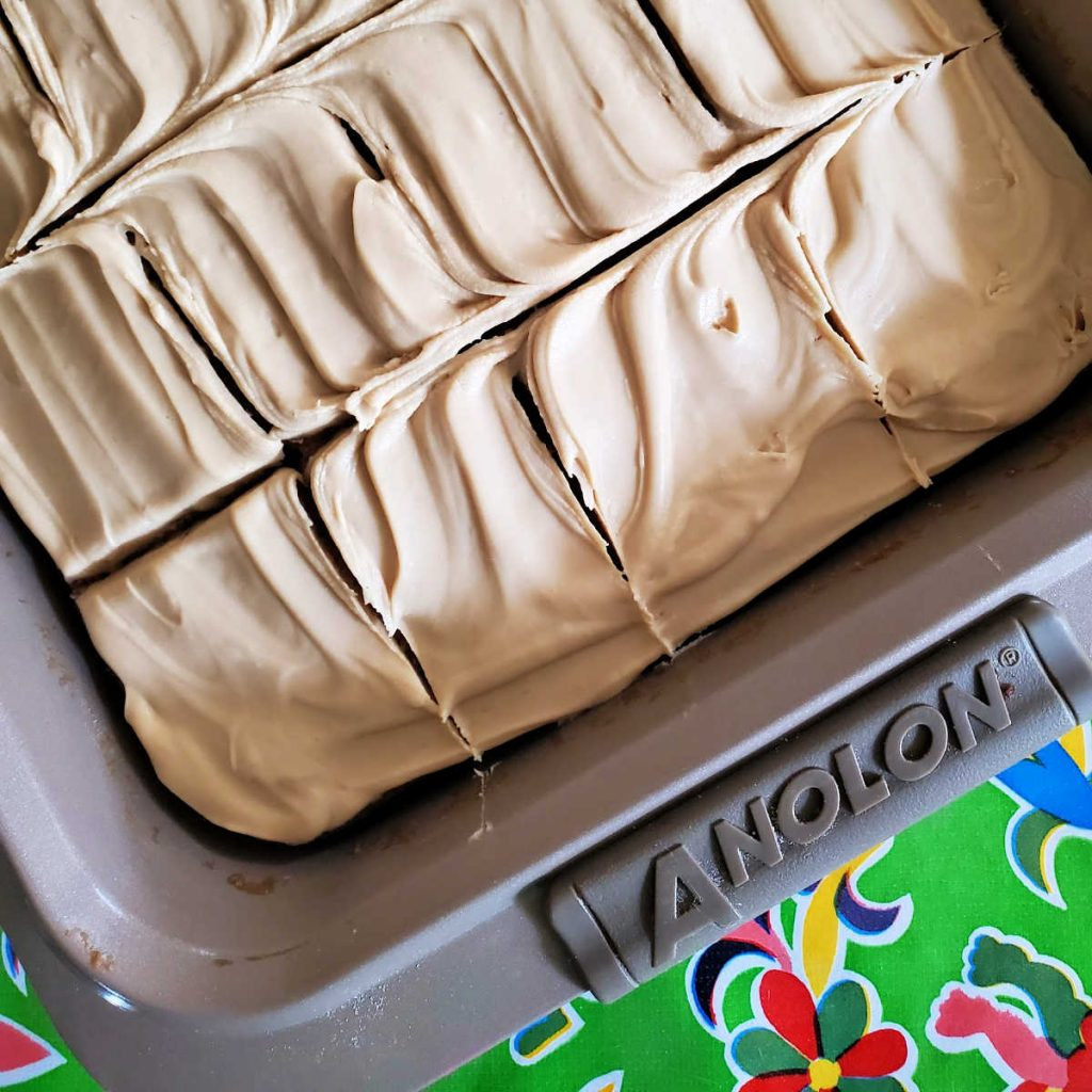 A frosted butterscotch sheet cake in a pan, showing cuts, ready for serving.