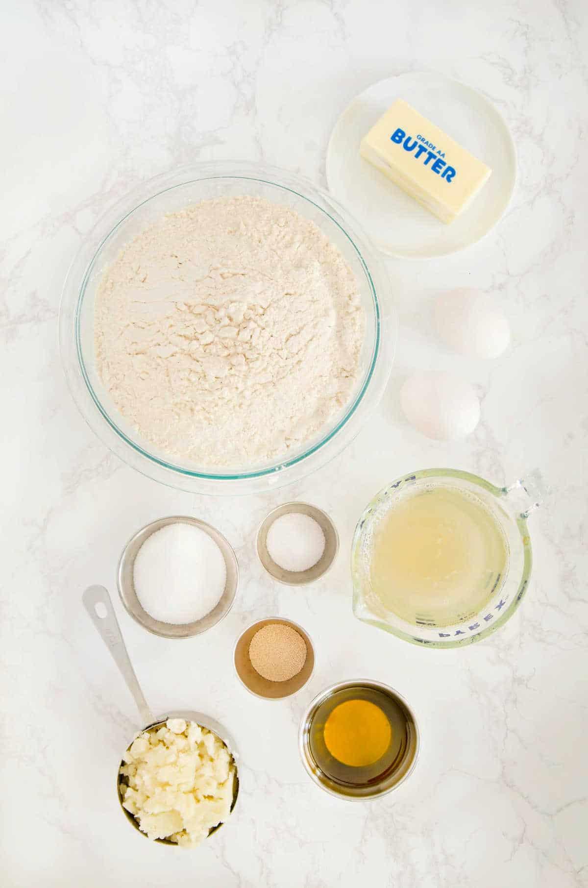 Overhead shot of bowls of ingredients for sandwich bread including flour,, butter, salt, mashed potato, potato water, etc.