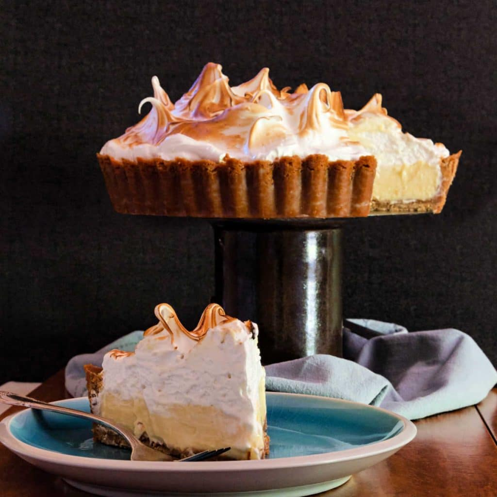 A lemon meringue tart on a pedestal and a slice on a plate ready for serving.