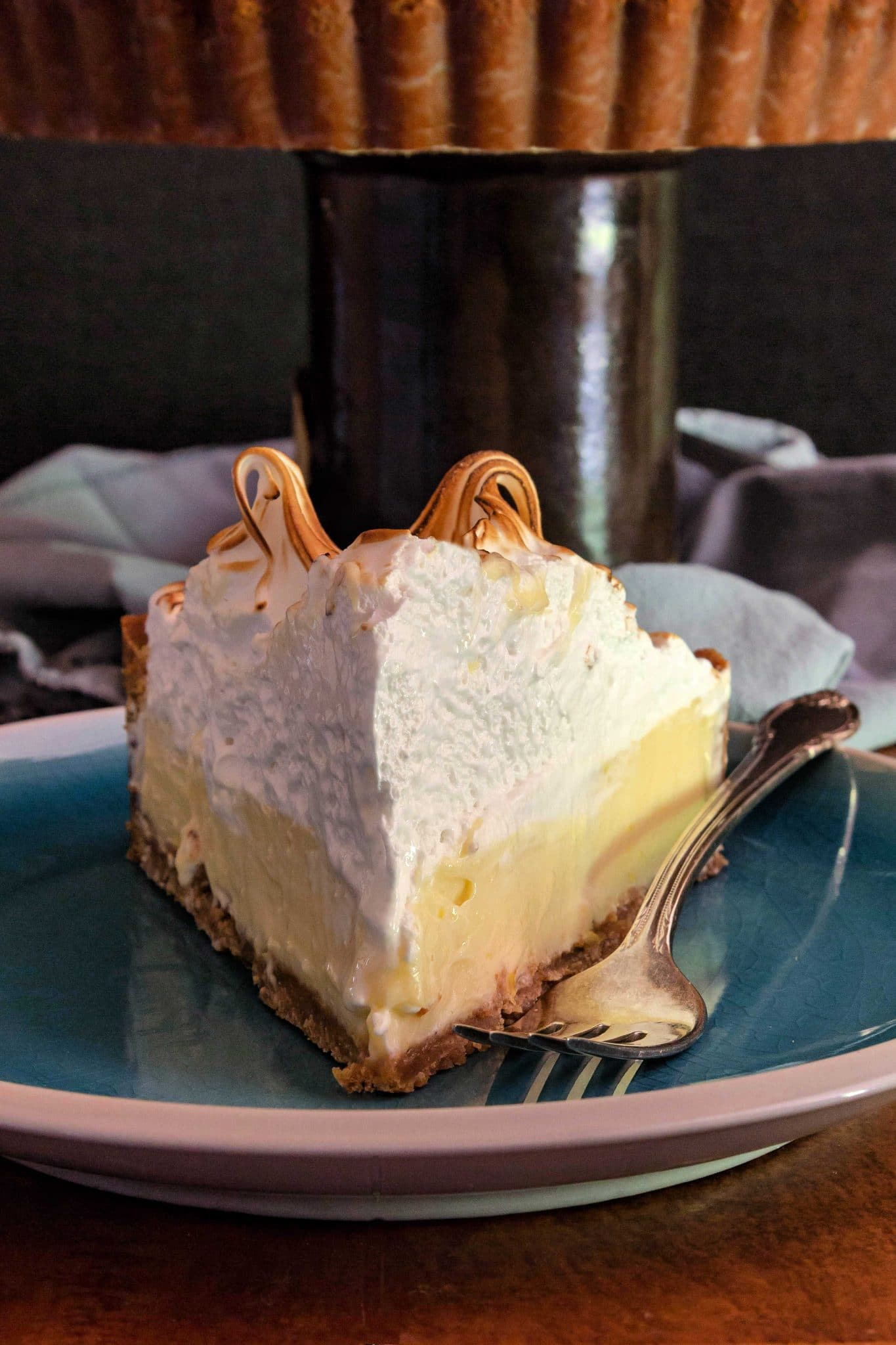 A close up of a slice of lemon meringue tart with a fork. Toasted meringue is clear.