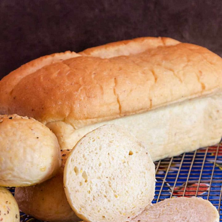 loaf of grits bread with a cut roll on a cooling rack