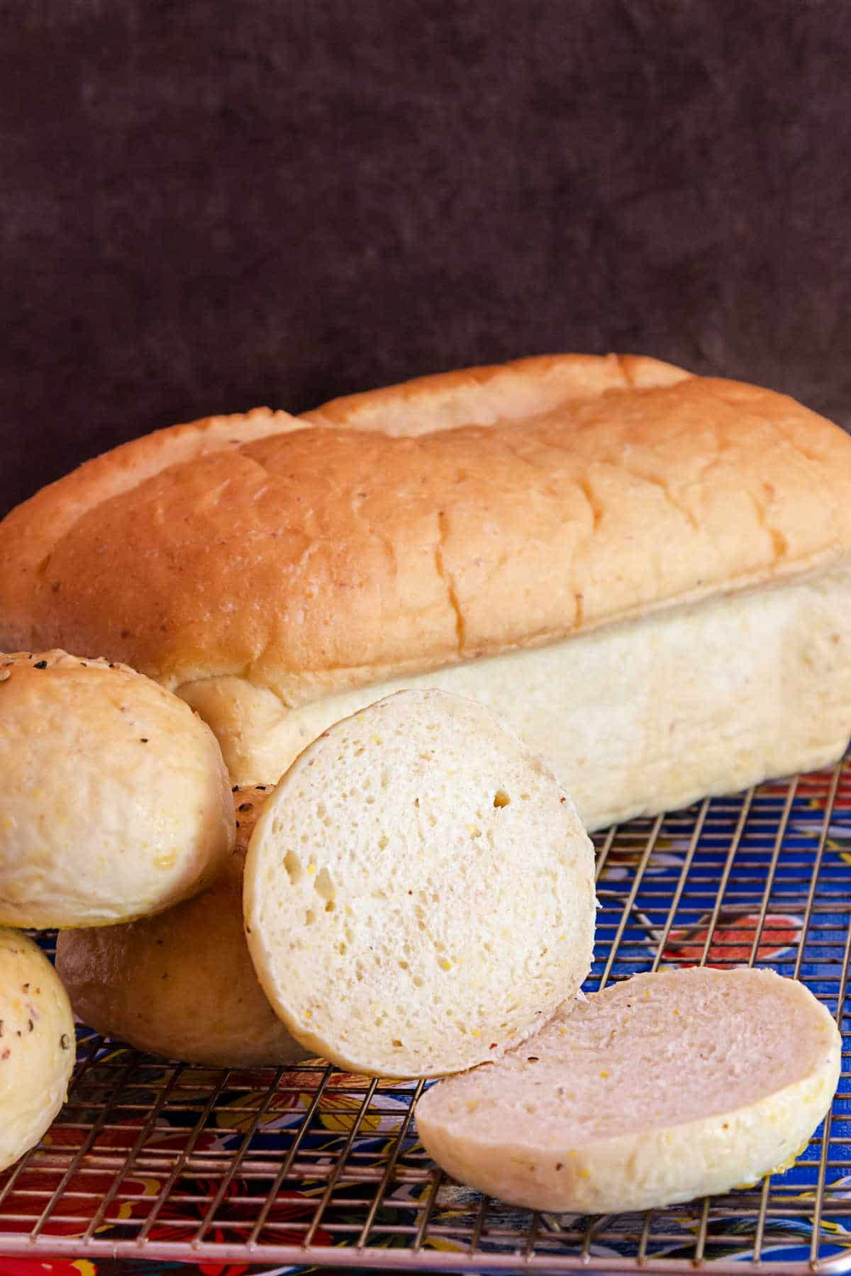 A fresh loaf of grits bread and a sliced bun on a cooling rack.