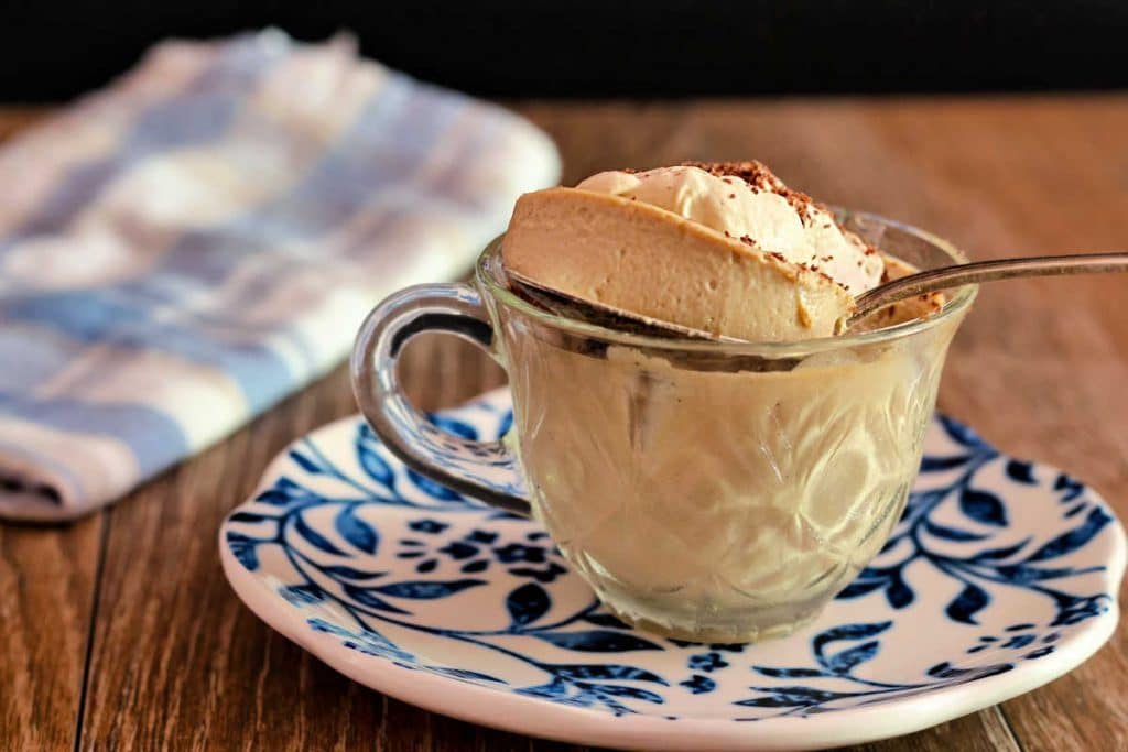 A bite of creamy beige Coffee panna cotta on a spoon coming out of a clear coffee cup on a blue and white plate.