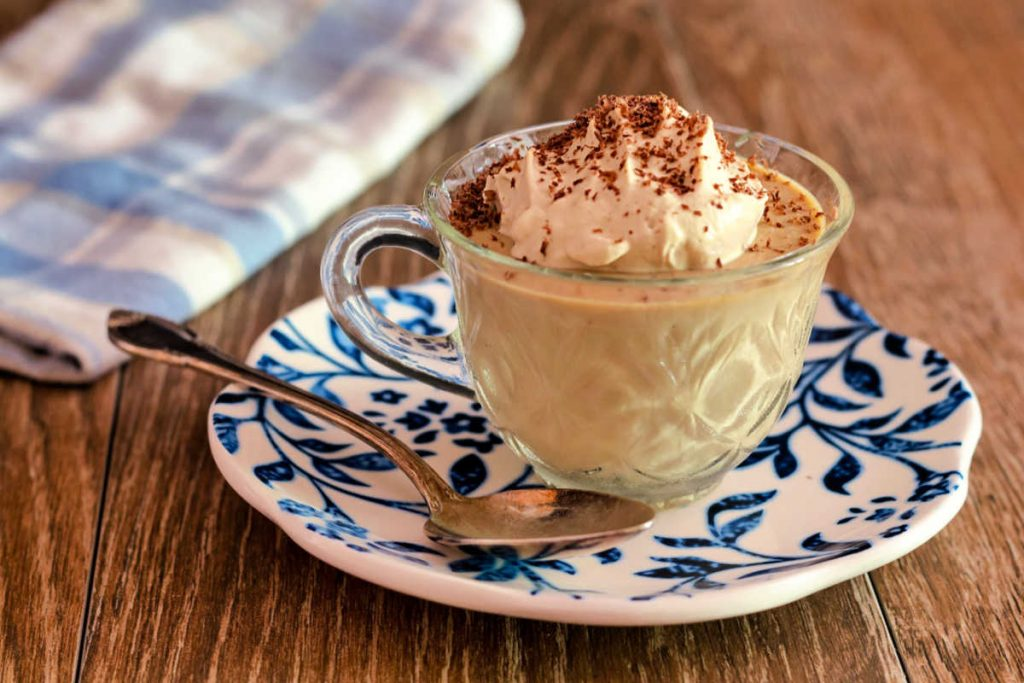 A clear coffee cup of panna cotta with whipped cream  and cocoa sprinkled on top on a blue and white plate.