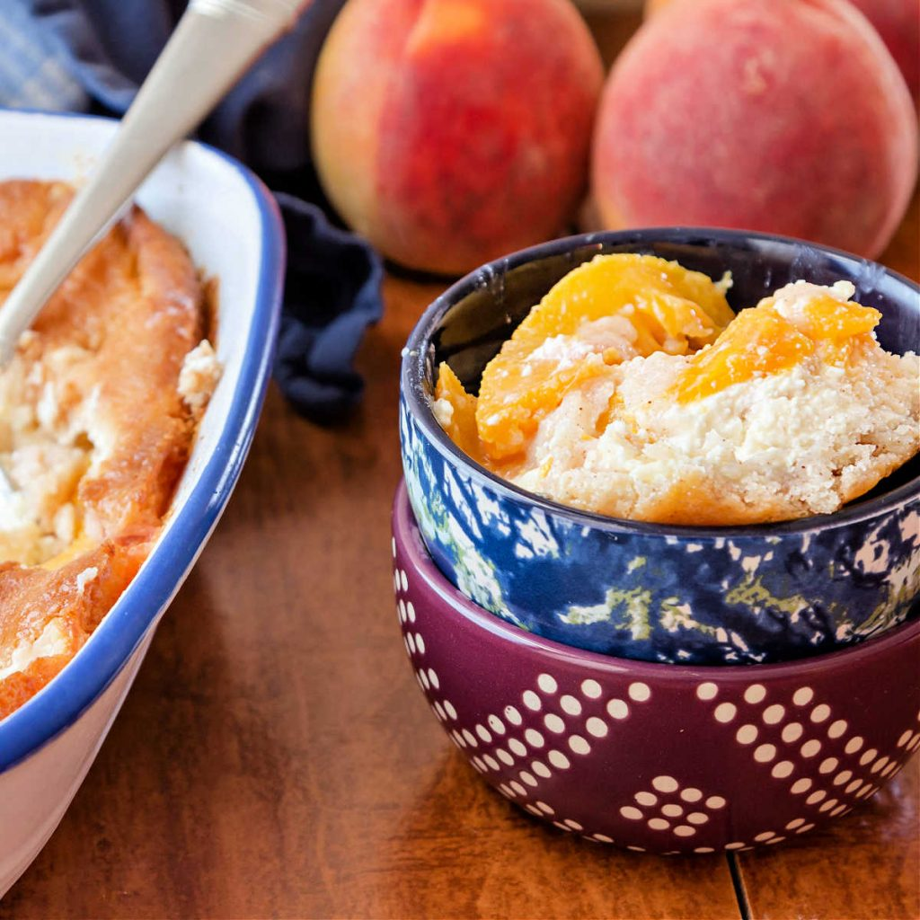 A  bowl of peaches and cream cobbler with next to baking dish with peach cobbler in it.