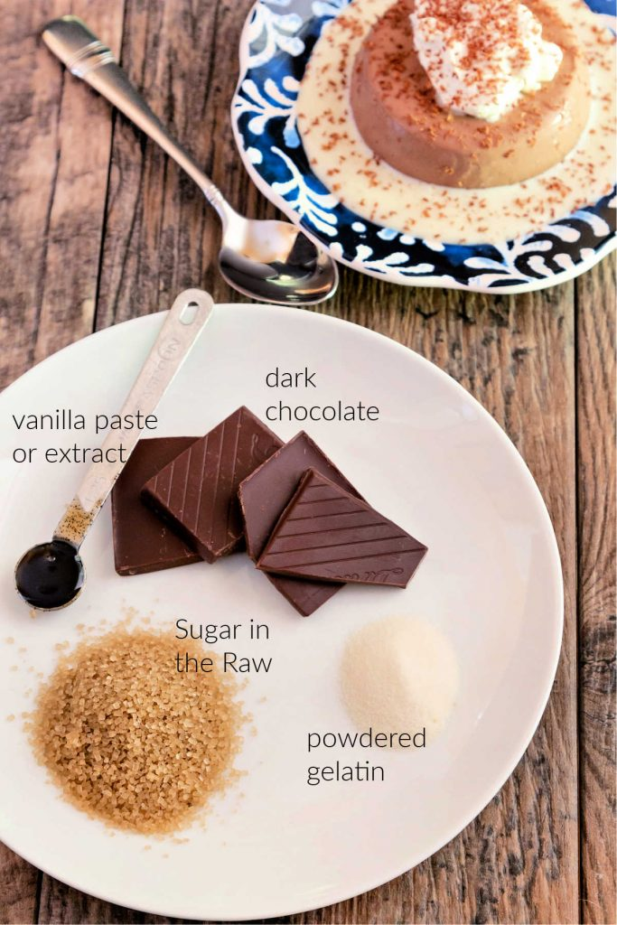 On a white plate, the panna cotta ingredients laid out, with text next to each. A metal measuring spoon with vanilla paste 9or vanilla extract) in it, squares of dark chocolate, a small mound of dry powdered gelatin, a mound of brown sugar in the raw granules.