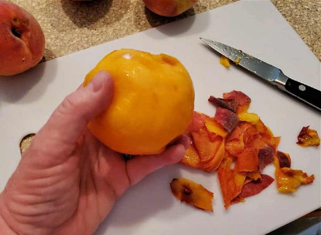 A hand holding a peeled peach with peelings and a paring knife on a cutting board.