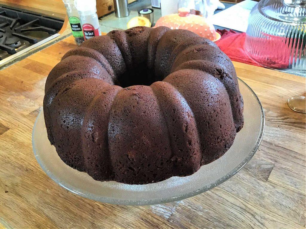 Chocolate pound cake, not yet glazed, on a glass cake stand.