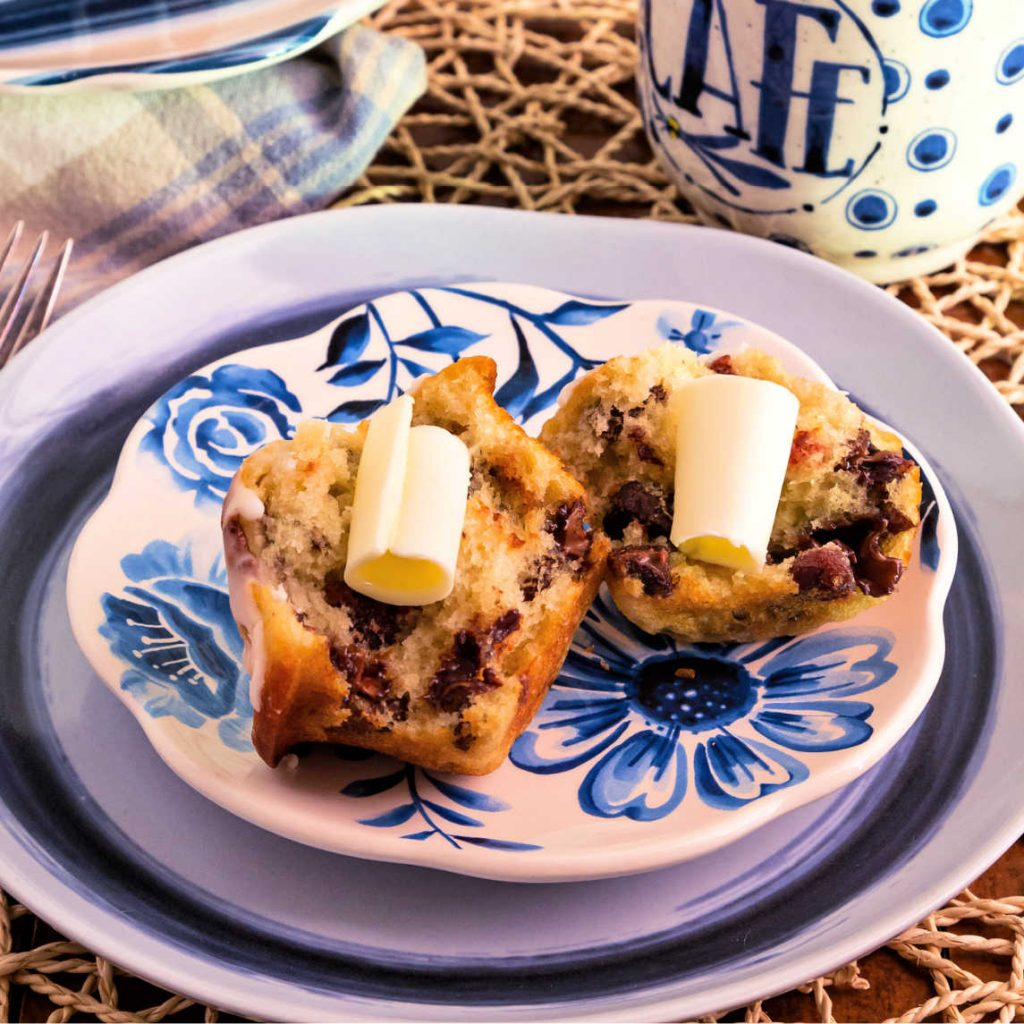 A split buttermilk muffin with cherries, chocolate, and pecans served with curls of butter.