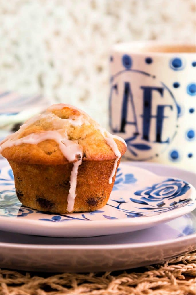 A glazed chocolate chip muffin on a plate with a cup of coffee ready for serving.