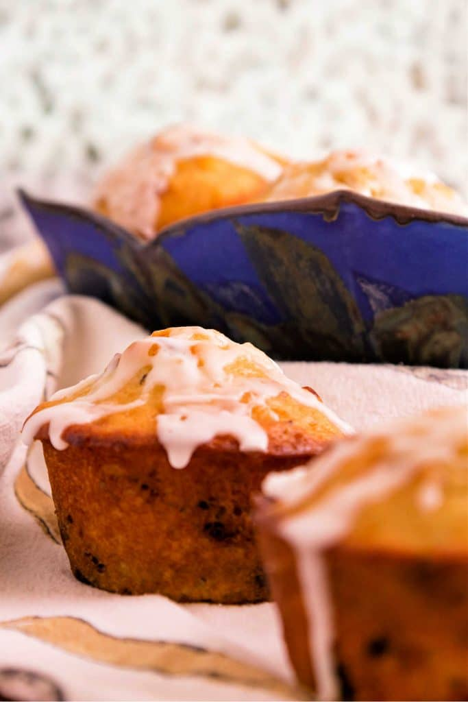 Two glazed buttermilk muffins with a blue bowl of muffins in the background.