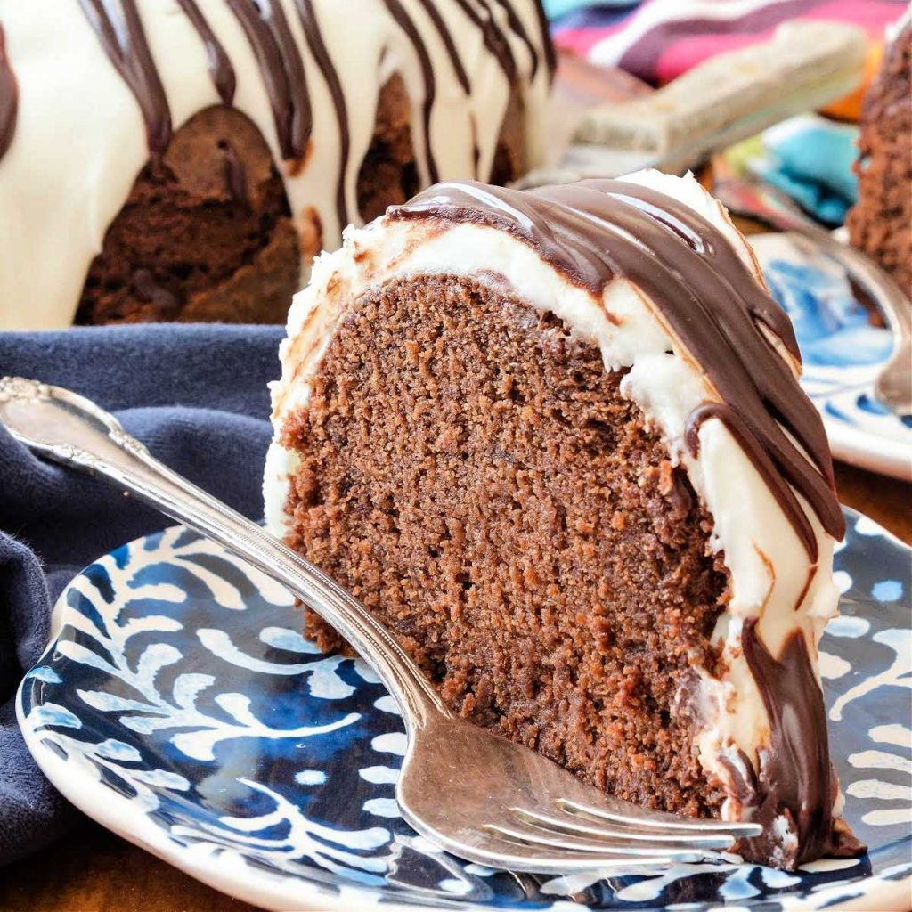 A slice of glazed chocolate pound cake with a fork on a blue plate.