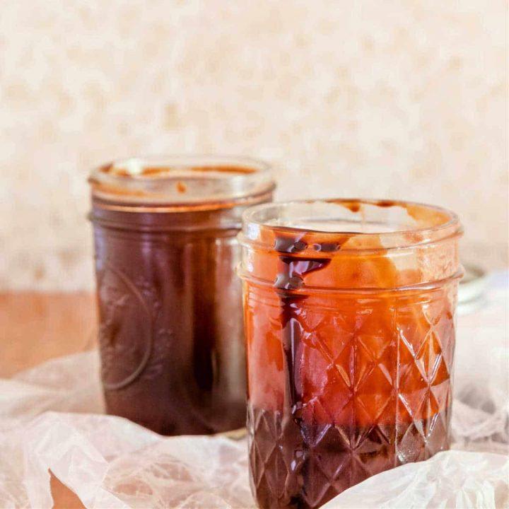 a full jar and a half full jar of homemade chocolate sauce