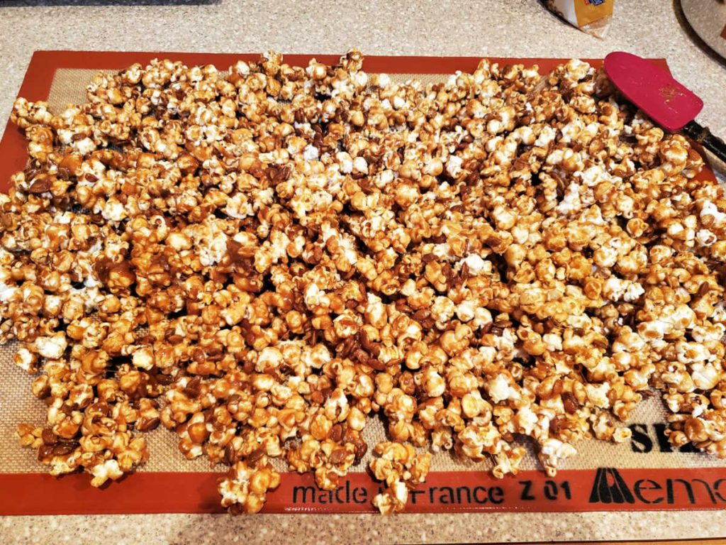 Pumpkin spice caramel corn spread out to cool on a Silpat.